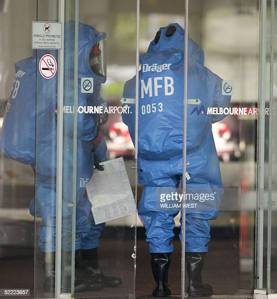 Firemen enter the terminal in protective clothing after staff members of airline Virgin Blue were struck down by a mystery illness which spread...