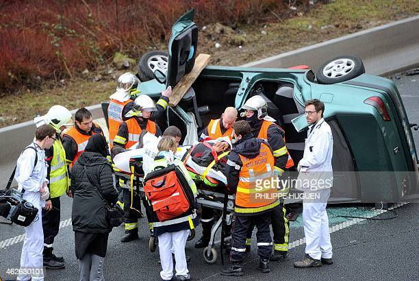 Firemen evacuate a man on a stretcher following a car crash on January 2014 on Roubaix's ringroad AFP PHOTO PHILIPPE HUGUEN