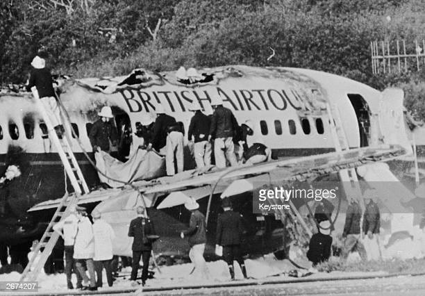 Firemen examining the wreckage of a British Airtours Boeing 747 which burst into flames during take off at Manchester Airport, killing 54...