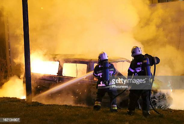 Firemen extinguish the burnt out remains of the van used in the heist near Brussels Airport on February 18 2013 in Zaventem Belgium Using a van and...