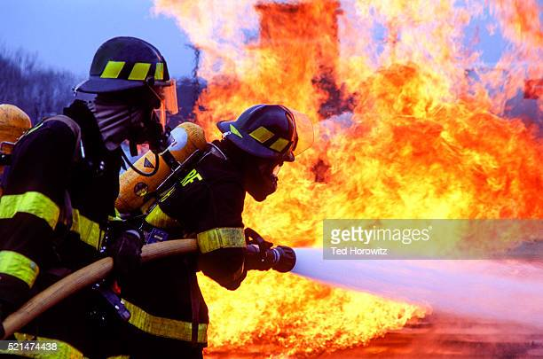 firemen fighting blaze with hose. - firefighter stock pictures, royalty-free photos & images