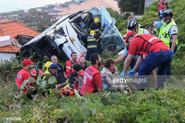 TOPSHOT Firemen help victims of a tourist bus that crashed on April 17 2019 in Caniço on the Portuguese island of Madeira At least 28 people were...