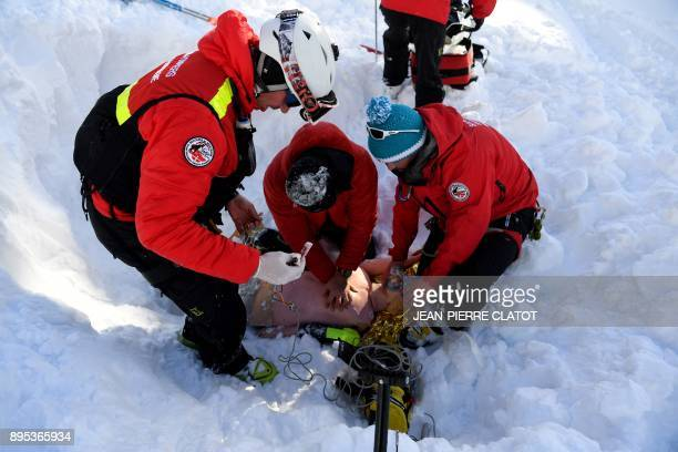 Firemen hold a dummy during a mock rescue operation during an avalanche exercice on December 19 2017 in Les Gets / AFP PHOTO / JEANPIERRE CLATOT