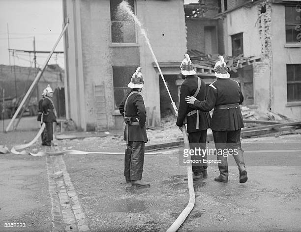 Firemen hosing down a house at Chatham, Kent, on which a bomb was dropped in an air-raid exercise.