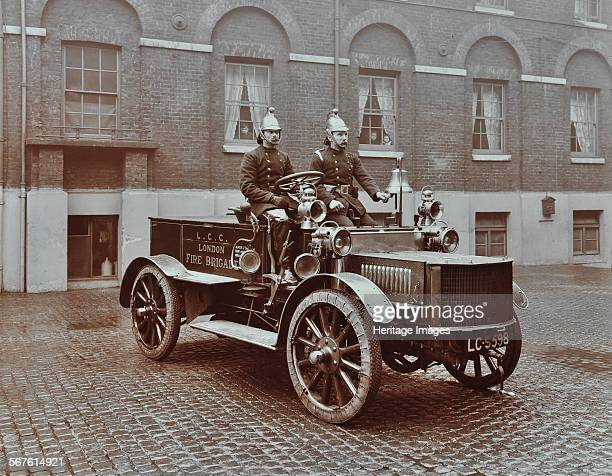 Firemen in brass helmets aboard a motor hose tender London Fire Brigade Headquarters London 1909 Moustached firemen pose on a vehicle one is ringing...