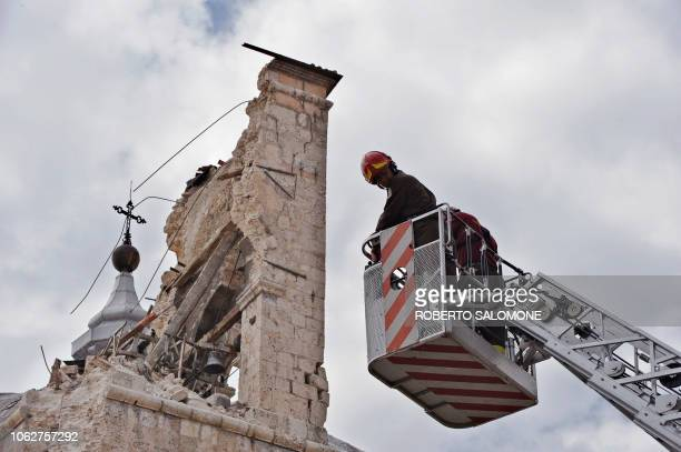 Firemen inspect the bell tower of San Bernardino church on April 9, 2009 in the Abruzzo capital L'Aquila. Italian Prime Minister Silvio Berlusconi...