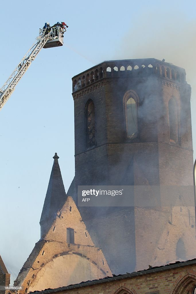 Firemen inspect the remains after a fire destroyed the Sint-Niklaas church (Sint-Niklaaskerk) in Westkapelle, part of Knokke-Heist municipality, on March 26, 2013.