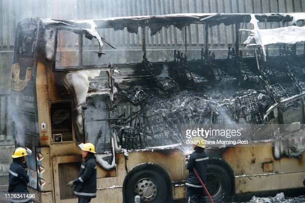 Firemen inspecting the wreckage of a Kowloon Motor Bus which was on fire about 900am at the Hong Kong Island side of the Eastern Harbour Tunnel 27...