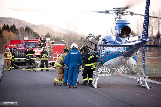 firemen load a gurney into waiting helicopter - medevac stock photos and pictures