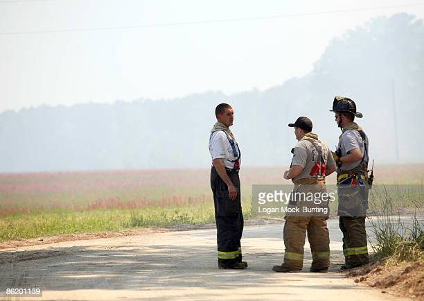 Firemen monitor backfires lit by the Forestry Service meant to contain wildfires April 24 2009 in Horry County North Carolina The backfires are meant...