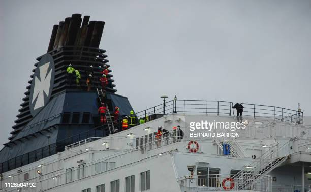 Firemen of the Grimp attempt to get migrants to come down from a ferry funnel on March 3 2019 in the northern French port of Calais after migrants...