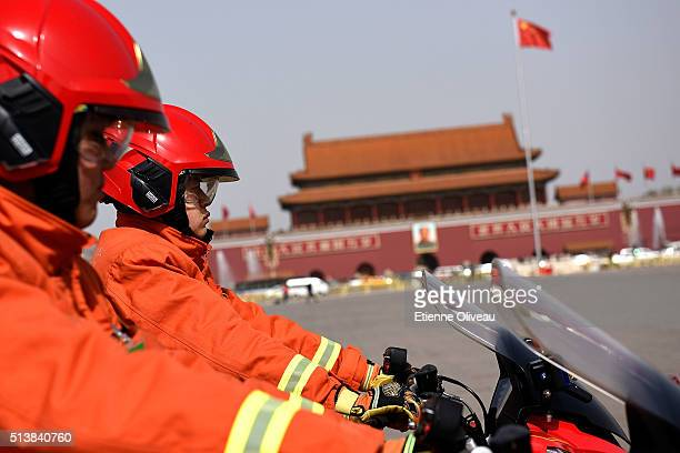 Firemen on motorbike stands in front Tiananmen during the opening session of the China's National People's Congress on March 5 2016 in Beijing China...