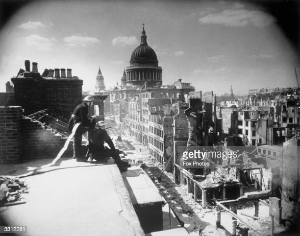Firemen on the roof of Cannon Street Station looking towards St Paul's Cathedral London