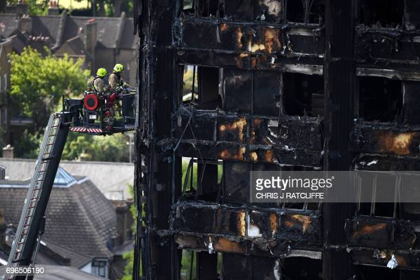 TOPSHOT Firemen perched on an extendable ladder raise inspect the remains of Grenfell Tower a residential tower block in west London which was gutted...