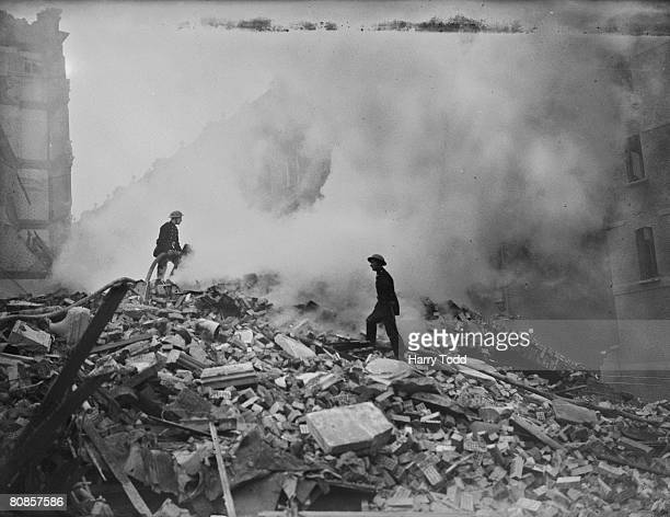 Firemen playing their hoses on the smouldering debris left after a German bombing raid on London during the Blitz 16th October 1940