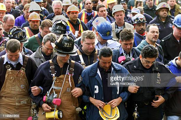 Firemen police officers and workers lock arms while observing a moment of silence during a short interfaith memorial service held at the World Trade...