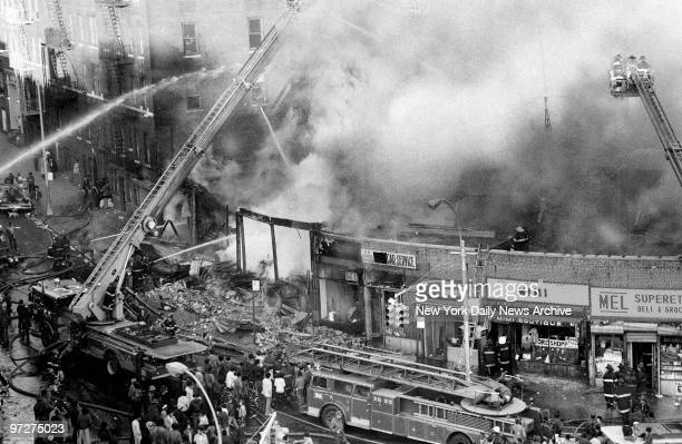 Firemen pour water on a threealarm fire that erupted about 3pm yesterday in a row of 12 stores at Burnside and Harrison Aves Five stores burned Two...