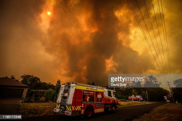 Firemen prepare as a bushfire approaches homes on the outskirts of the town of Bargo on December 21, 2019 in Sydney, Australia. A catastrophic fire...
