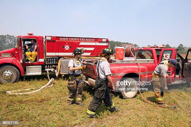 Firemen prepare to monitor backfires lit by the Forestry Service meant to contain wildfires April 24 2009 in Horry County North Carolina The...