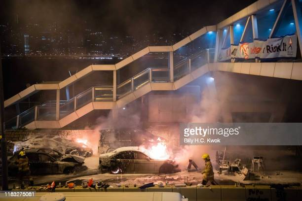Firemen put out a burning car set on fire by protesters near Hong Kong Polytechnic University in the Tsim Sha Tsui district on November 18 2019 in...
