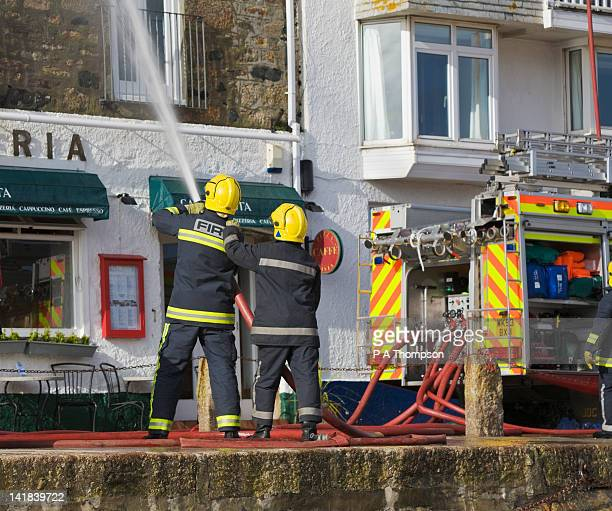 Firemen putting out building fire, St Ives, Cornwall, England