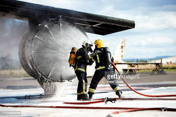 firemen putting out fire on old training aeroplane, darlington, uk - firefighter stock pictures, royalty-free photos & images