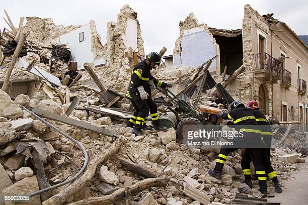 Firemen recover a rotavator from the rubble of earthquake-damaged homes on April 13, 2009 in L'Aquila, Italy. Recovery and clear-up efforts have...