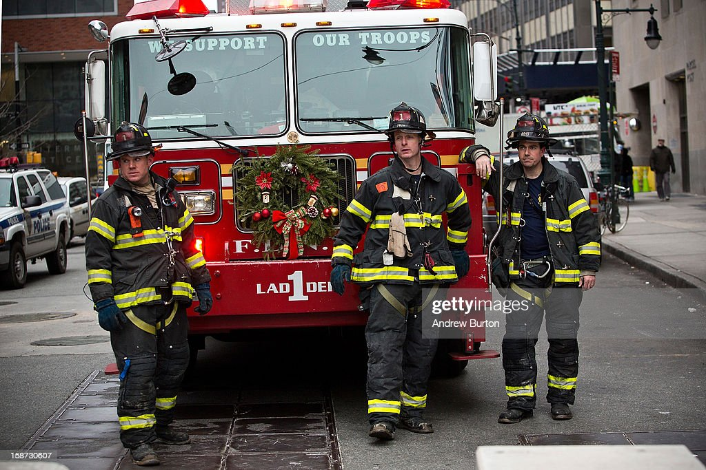 Firemen relax next to their fire truck after responding to a two-alarm fire at the World Trade Center on December 26, 2012 in New York City. The fire, which broke out in the construction trailers surrounding the World Trade Center building, was quickly contained.