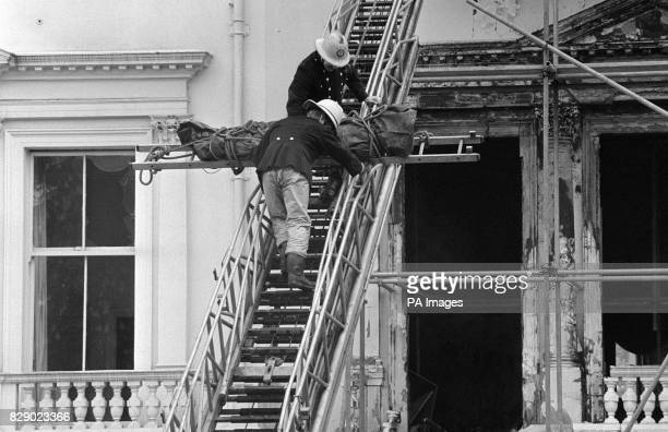 Firemen removing one of two bodies so far found in the burntout remains of the Iranian Embassy in London The corpse wrapped in a dark green body bag...