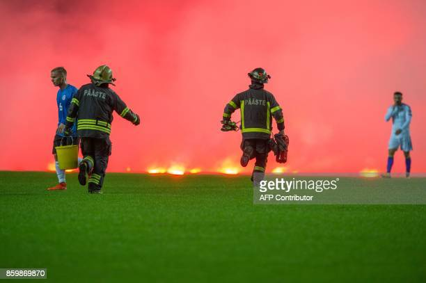 Firemen run on the pitch to take care of flares thrown by Bosnia fans during the FIFA World Cup 2018 qualification football match between Estonia and...