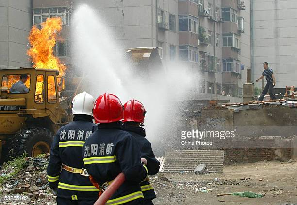 Firemen spray water at a bulldozer which caught fire after a Chinese man hurled Molotov cocktails at law enforcement officers to protest about his...