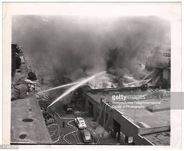 Firemen spray water on a large fire in a garage as men observe from a rooftop across the street New York New York 1940s Photo by Weegee/International...