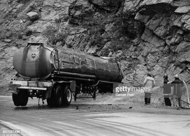 Firemen spray water onto spilled gasoline from this vice malfunctioned dropping the tanker onto the hightanker on US 6 in Clear Creek Canyon three...