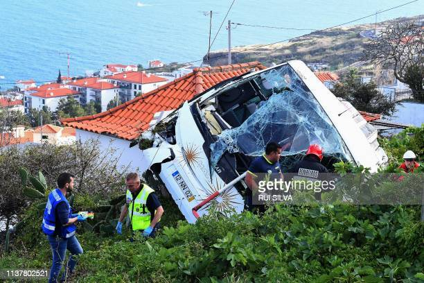 Firemen stand next to the wreckage of a tourist bus that crashed on April 17 2019 in Caniço on the Portuguese island of Madeira At least 28 people...