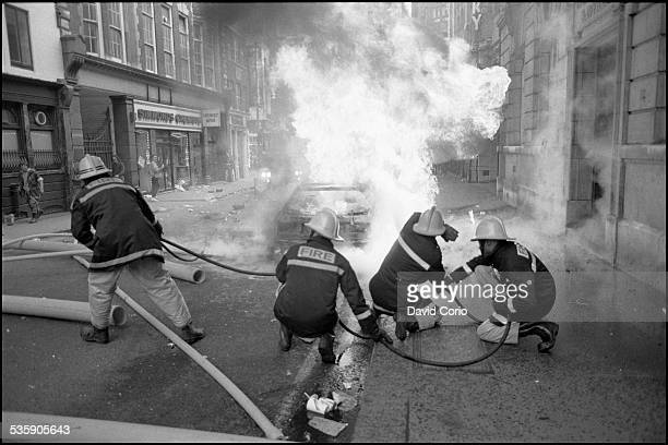 Firemen tackle a burning car during the Poll Tax demonstration in the West End of London UK 31st March 1990