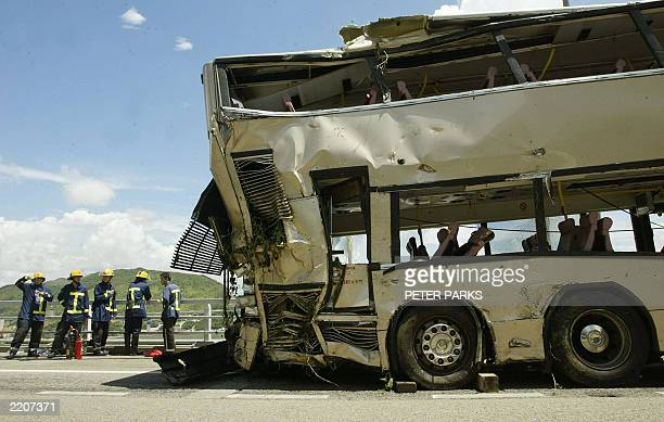 Firemen take a rest next to the wreckage of a double decker bus after it was lifted back on the road from which it crashed through a highway barrier...