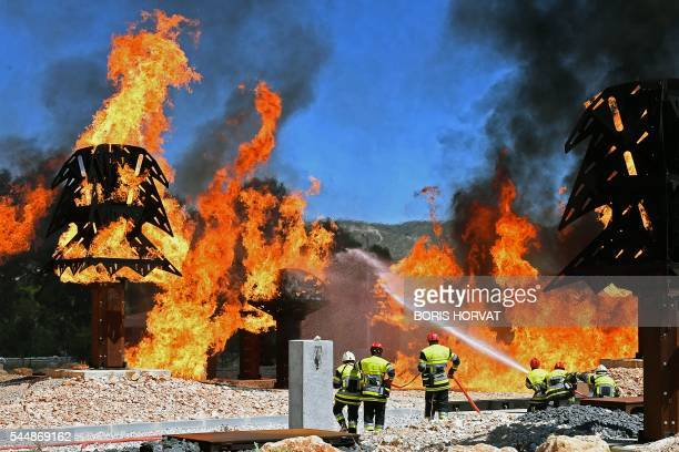 Firemen take part in a firefighting exercise at the fire brigade training centre in Velaux on July 4 where a forest fire was replicated within a...