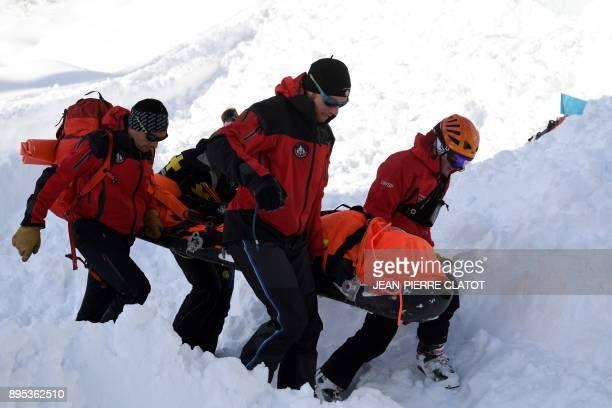 Firemen take part in a mock rescue operation during an avalanche exercice on December 19 2017 in Les Gets / AFP PHOTO / JEANPIERRE CLATOT