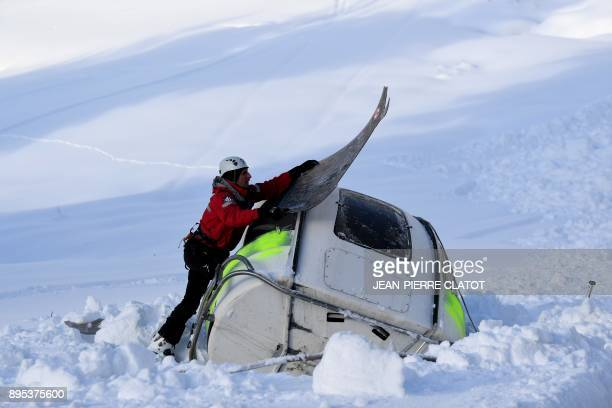 Firemen take part in a mock rescue operation near a cable railway cabin during an avalanche exercice on December 19 2017 in Les Gets / AFP PHOTO /...