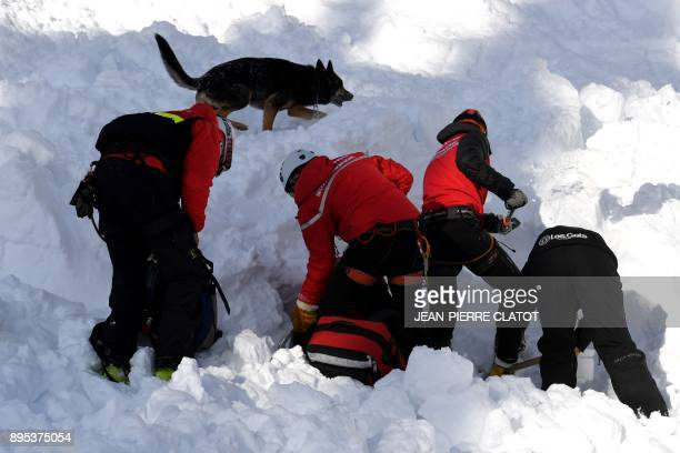 Firemen takes part in a mock rescue operation during an avalanche exercice on December 19 2017 in Les Gets / AFP PHOTO / JEANPIERRE CLATOT