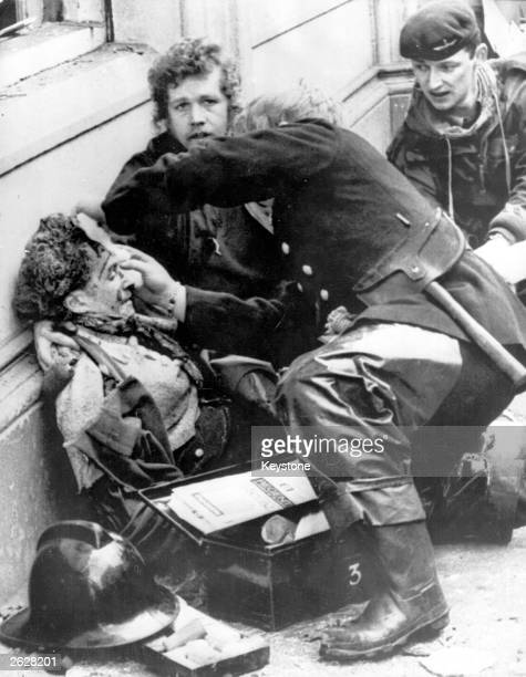 Firemen tend to a wounded victim of an Irish Republican Army car bomb explosion in Donegal Street Belfast The blast killed 6 people and injured 146