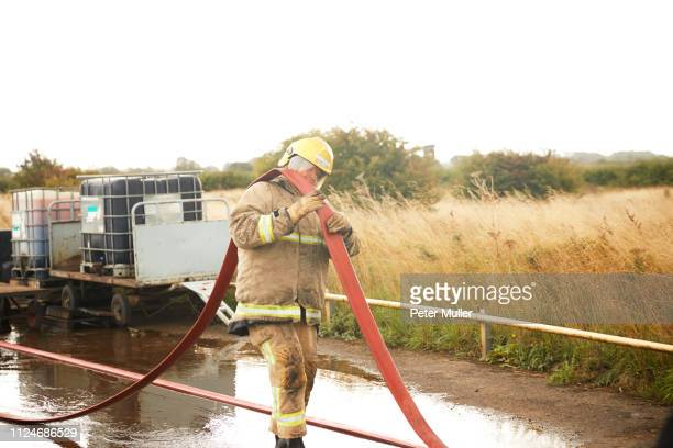 firemen training, fireman carrying fire hose over his shoulder at training facility - international firefighters day stock pictures, royalty-free photos & images
