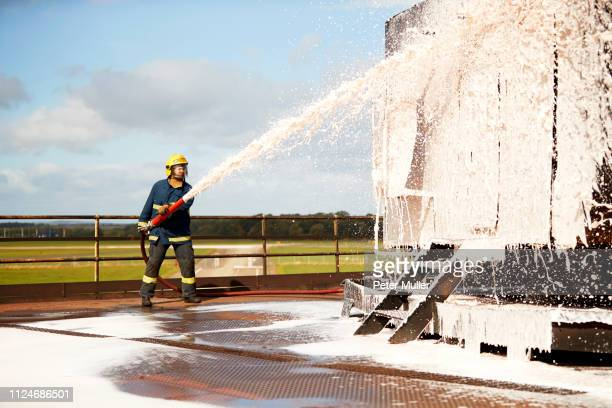 firemen training, fireman spraying firefighting foam at training facility - international firefighters day stock pictures, royalty-free photos & images
