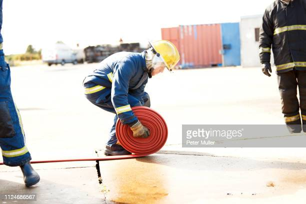 firemen training, fireman unrolling fire hose at training facility - international firefighters day stock pictures, royalty-free photos & images
