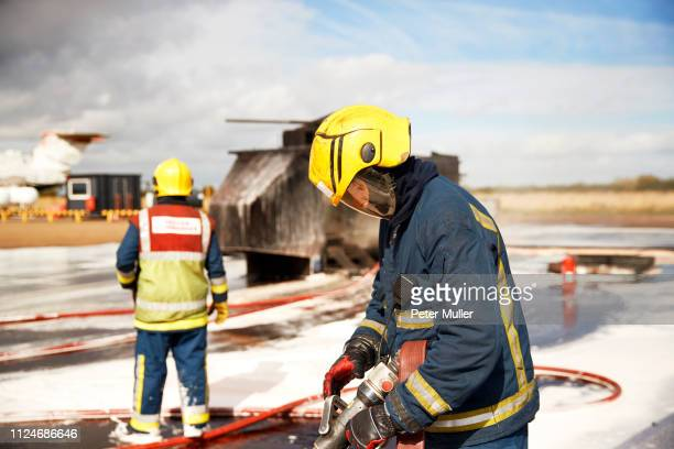 firemen training, firemen checking fire hose after mock helicopter fire at training facility - international firefighters day stock pictures, royalty-free photos & images