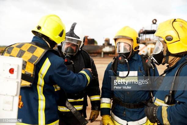firemen training, firemen in breathing apparatus listening to supervisor - international firefighters day stock pictures, royalty-free photos & images