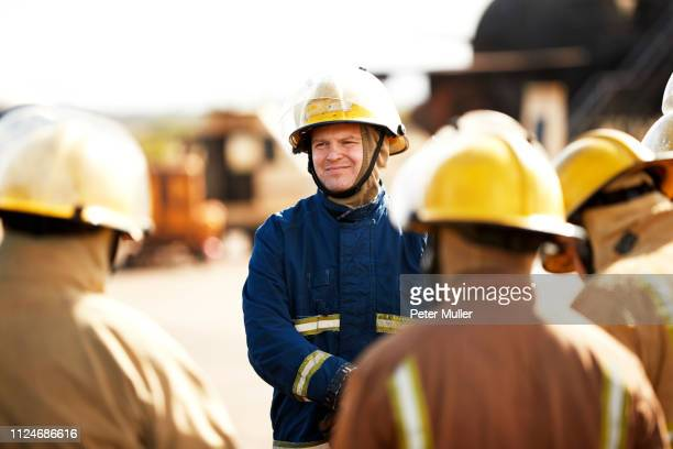 Firemen training, firemen listening to supervisor at training facility, over shoulder view