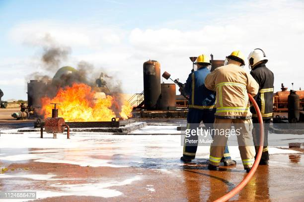 firemen training, firemen preparing to put out oil storage tank fire at training facility - international firefighters day stock pictures, royalty-free photos & images