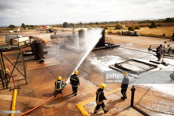 firemen training, firemen spraying firefighting foam at oil storage tank at training facility - fuel storage tank stock photos and pictures