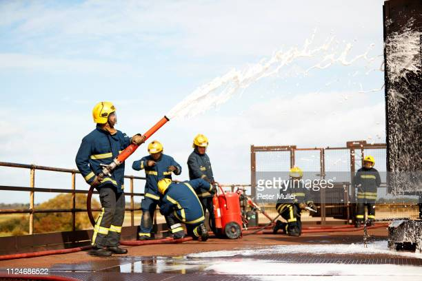 firemen training, firemen spraying firefighting foam at training facility - international firefighters day stock pictures, royalty-free photos & images